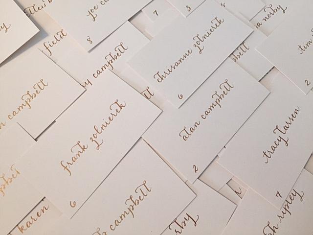 Escort cards written in gold ink