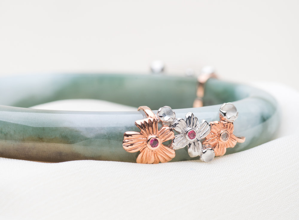 The Feminine - Sakura Jade BangleOpen the wardrobe of a feminine woman and you would find all things lovely, including countless number of ruffles, lace and flower prints. Among all the bangles, nothing speaks to The Feminine quite like the Sakura Jade Bangle. The Sakura is a favourite among many cultures for its beauty and fragility, symbolising the transience of life.