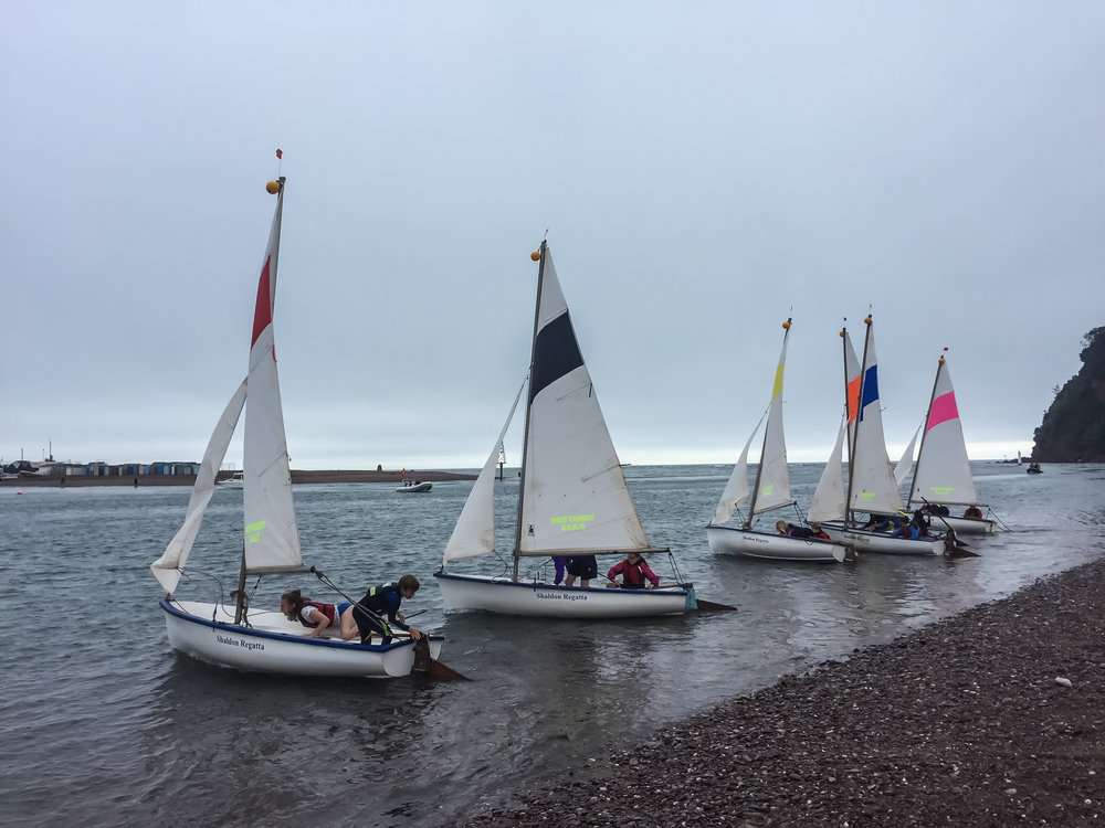 Our fleet of Otter sailing dinghies racing from the beach