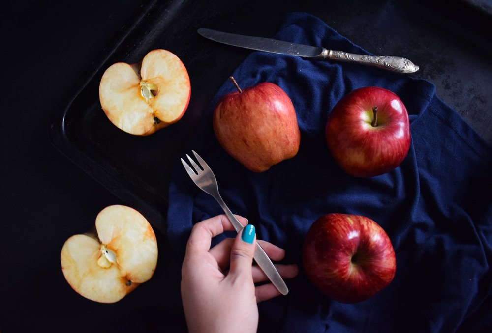 Woman holding a fork in her hand cutting the core or an apple out