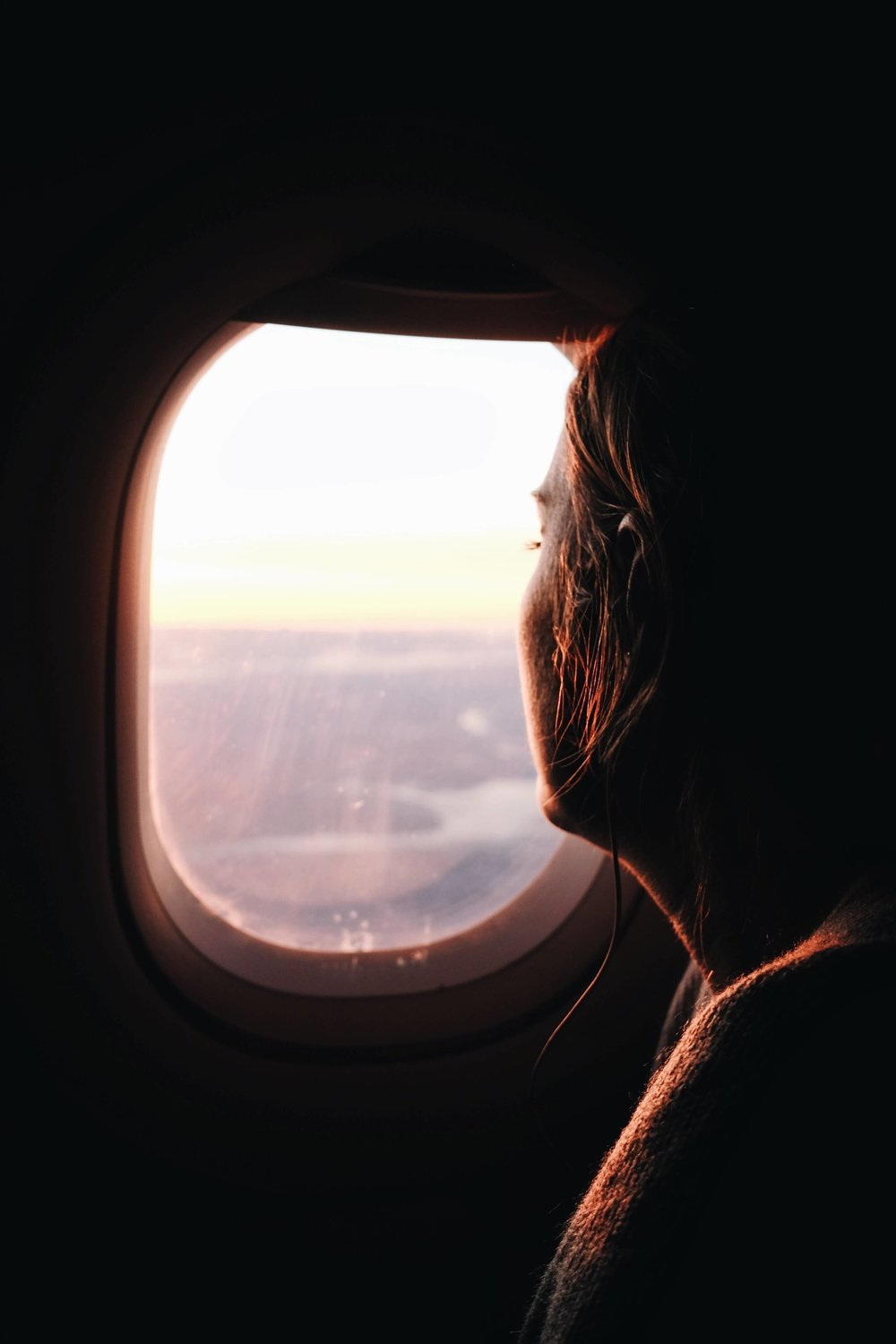 Woman looking out an airplane window