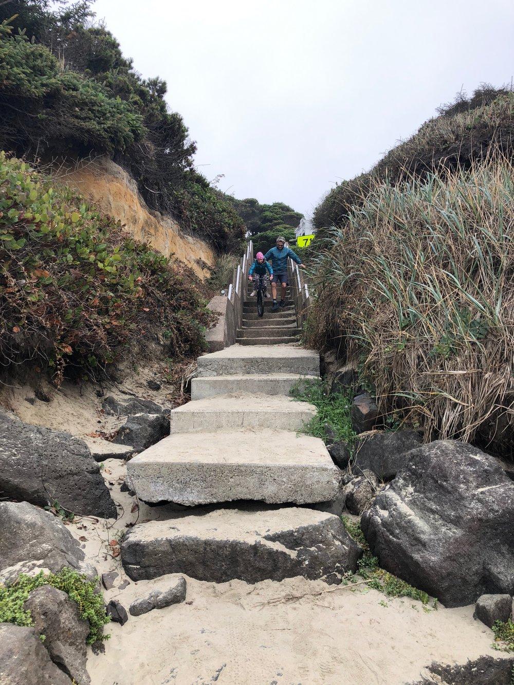 Isla biking down the stairs from camp to Tillicum Beach