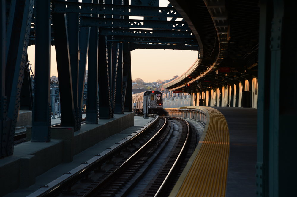 A photo of a subway train pulling into an above-ground station.