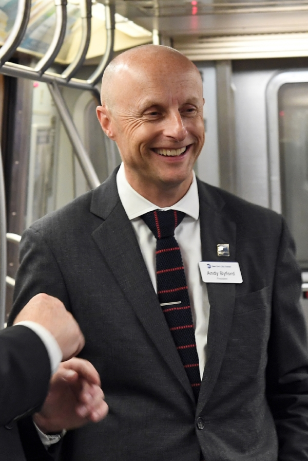 Andy Byford smiling and riding the subway.