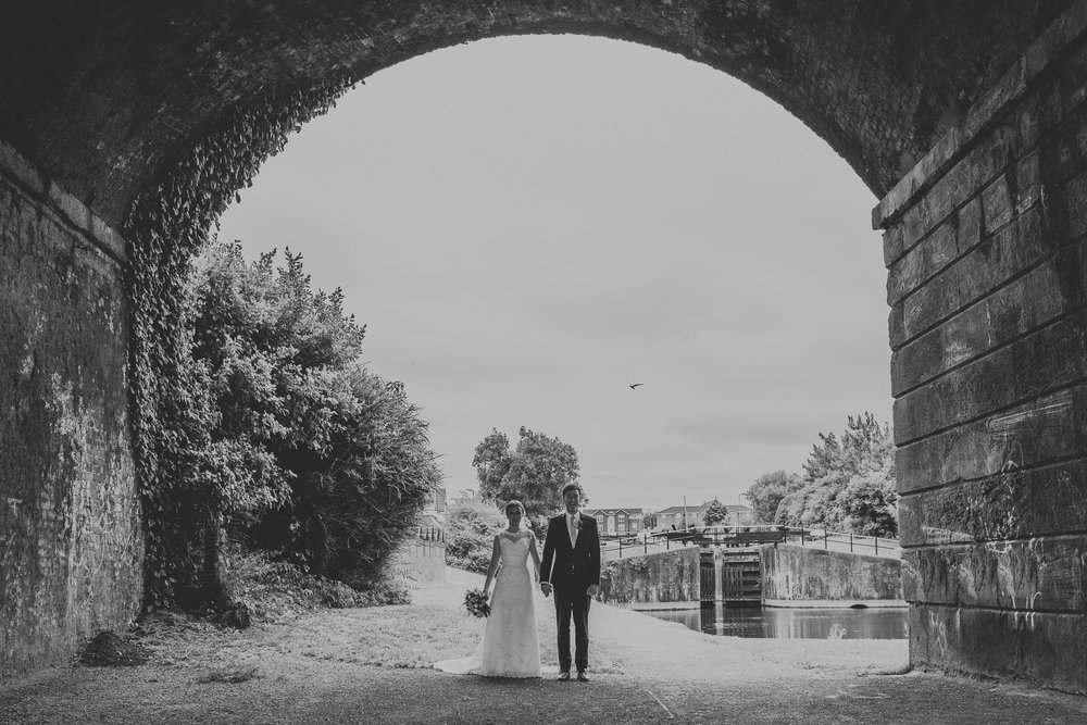 Jess and Ben - Liverpool wedding - bride and groom under a bridge holding hands