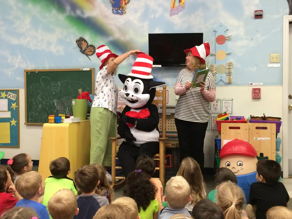 """ELC volunteers Kathy Stawawa and Teresa Widman reading the book """"Ten Apples Up on Top"""" by Dr. Seuss with special guest The Cat in the Hat during a Dr. Seuss program at Kids First Learning Center in Middleburg."""