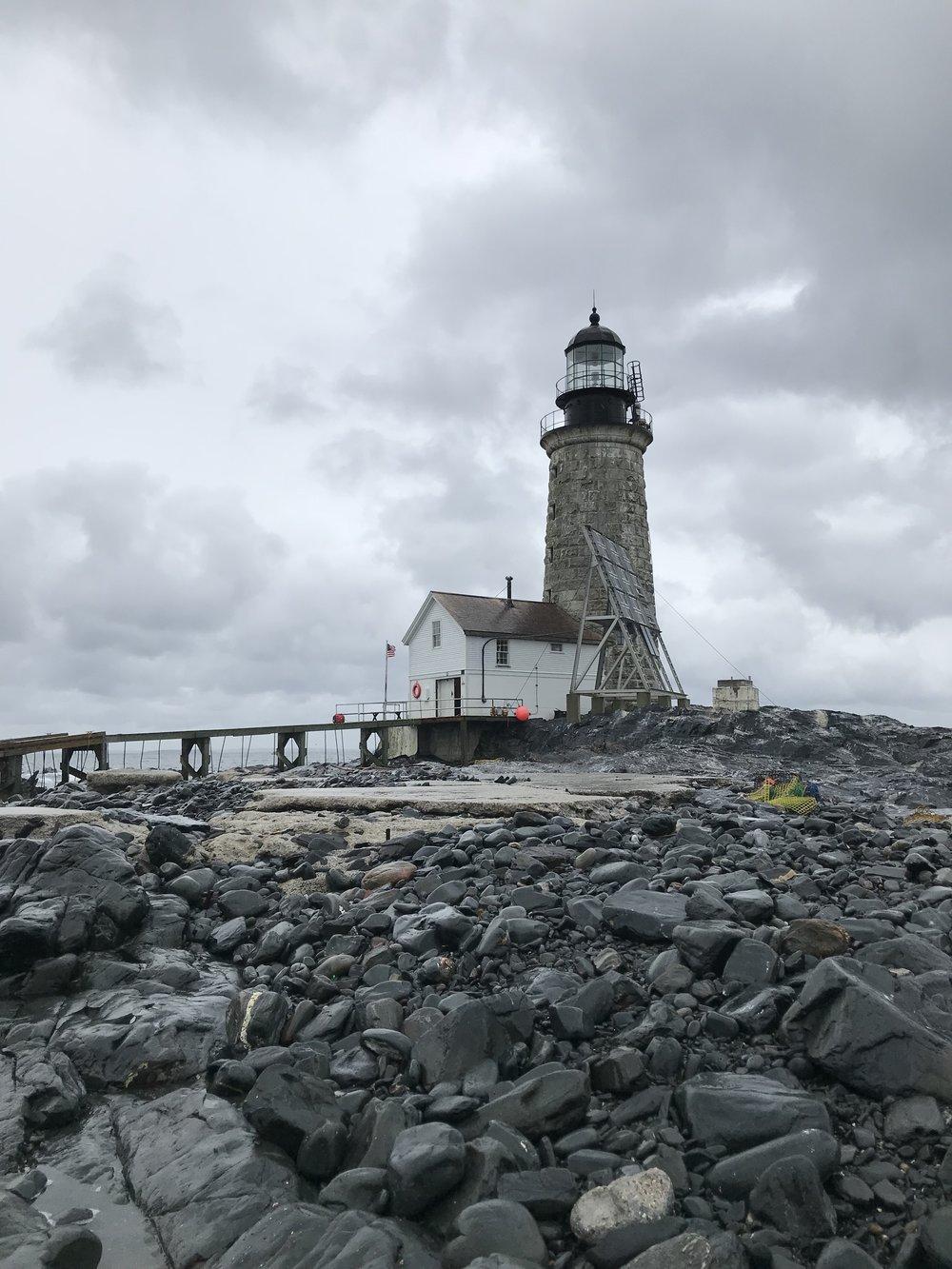 lighthouse on rocky coast on cloudy day