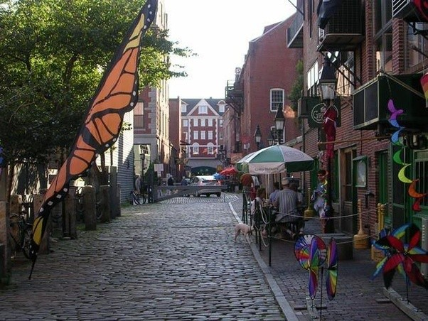 cobblestone Wharf Street with colorful flags and umbrellas
