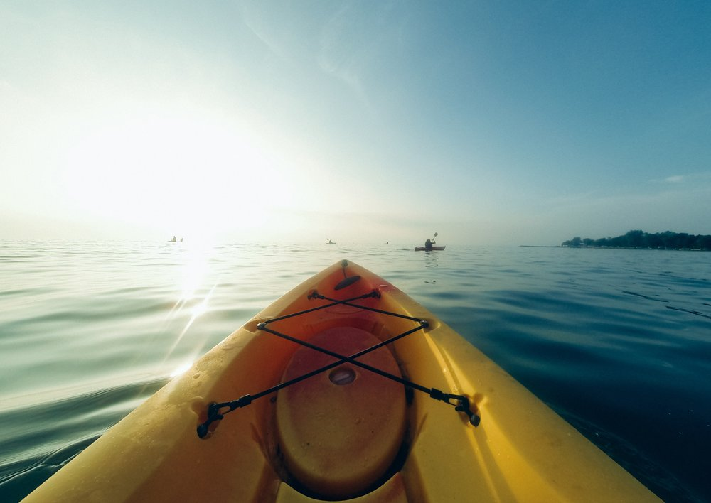 tip of yellow kayak in sunshine on water