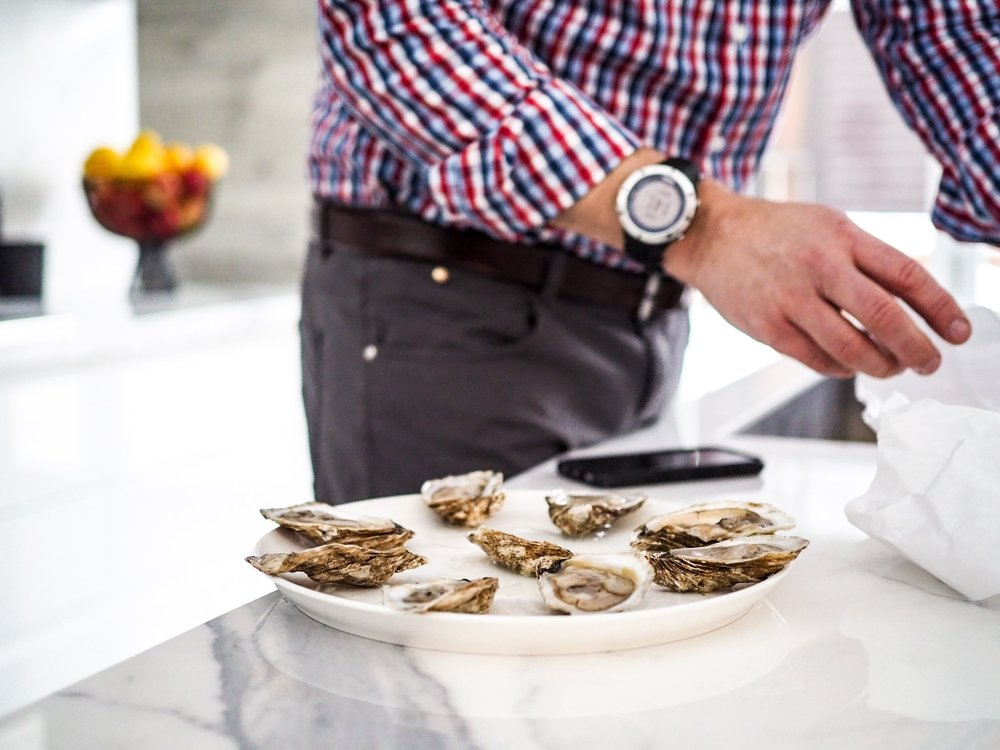 man preparing to cater with plate of oysters on the half shell