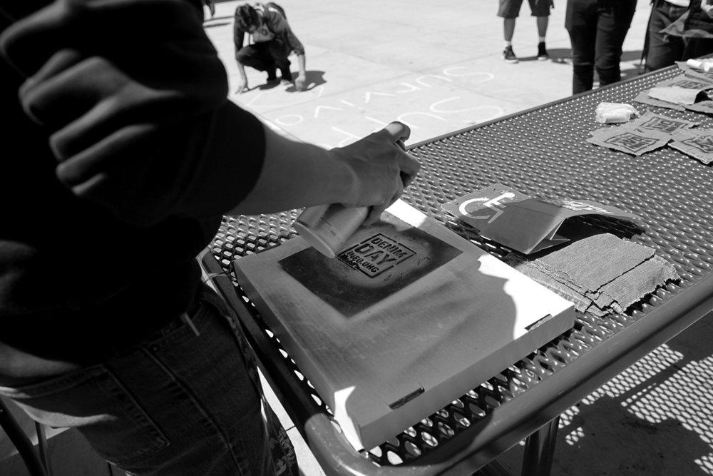 Students spray painting Denim Day stencils on jean pockets