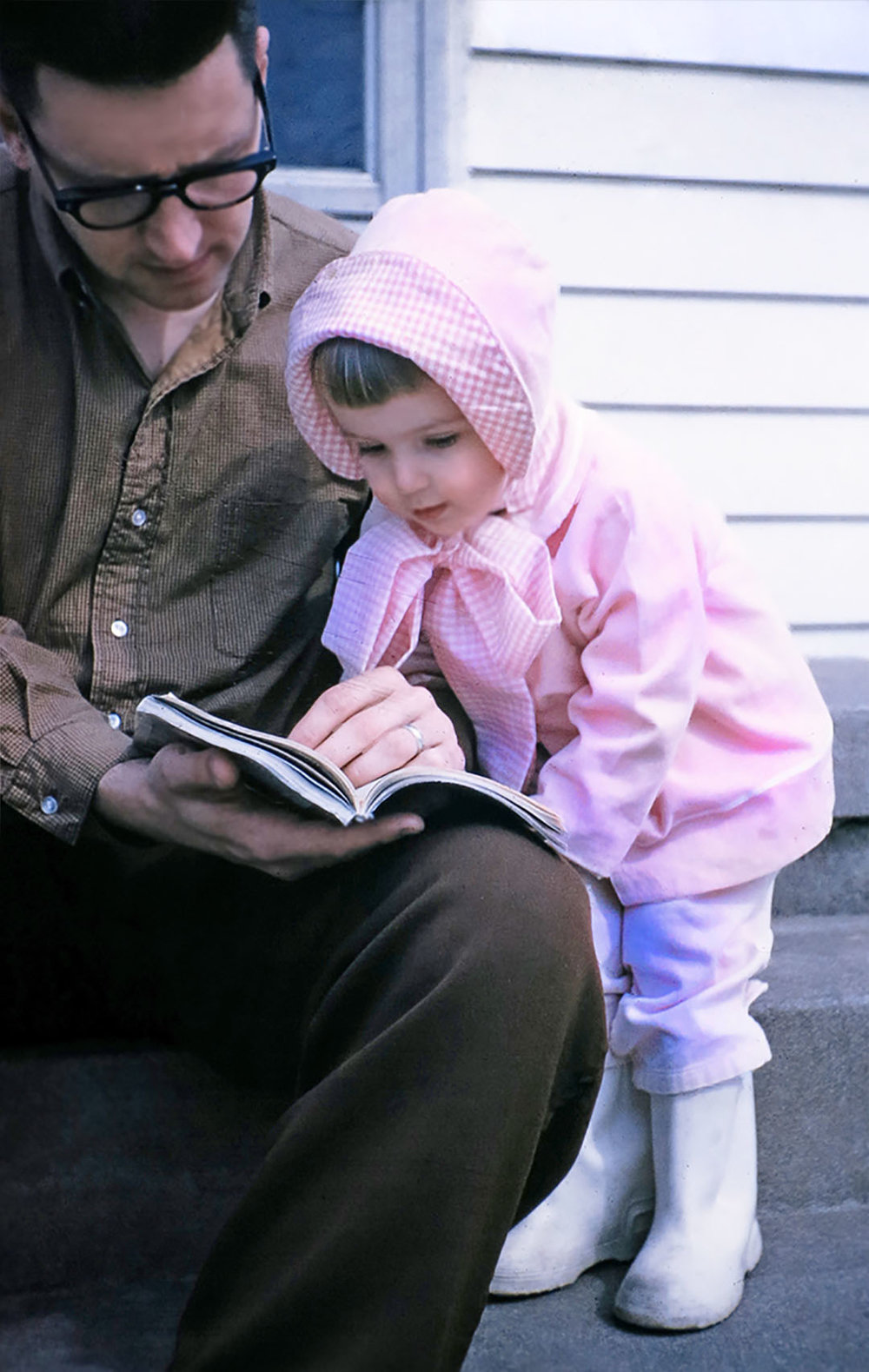 After the birthday party, bundled in a pink bonnet, reading a good book with Dad.