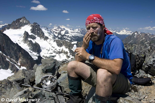 Mountaineer Steve Smith applies sunscreen on a bright day.Ragged Ridge, North Cascades Washington.