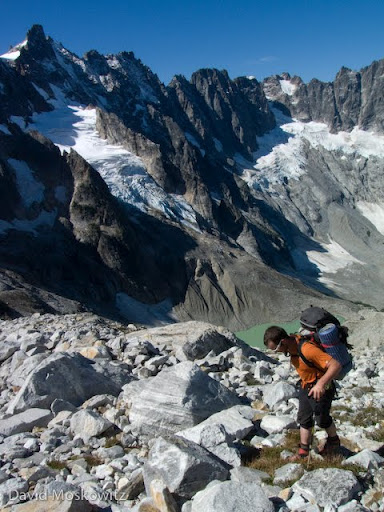 Forest McBrian hiking out of Luna Cirque with the massive north face of Mount Fury rising on the left and Luna lake below.