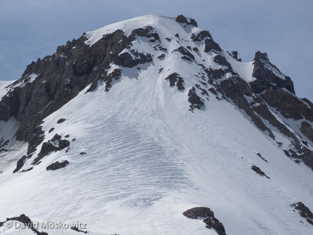 View of the final portion of the Cooper Spur route which ascends the wind sculpted lower slopes before weaving through the bands of rocks to reach the summit.