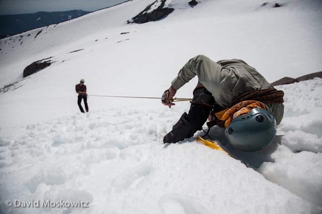 Outward Bound Instructor John Rudolph practicing his crevasse rescue skills–building a snow anchor and transferring the weight of a fallen climber from his harness to the anchor.