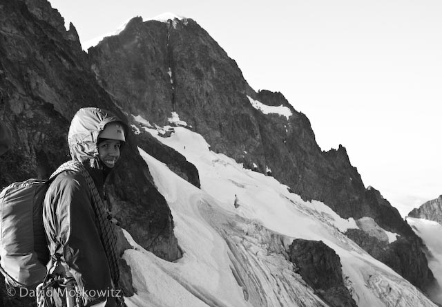 Samantha smiling at our first view of the route from the Dorado Needle Col which separates the McAlester Glacier from the Marble Creek Cirque. The climbing route is esentially the right skyline