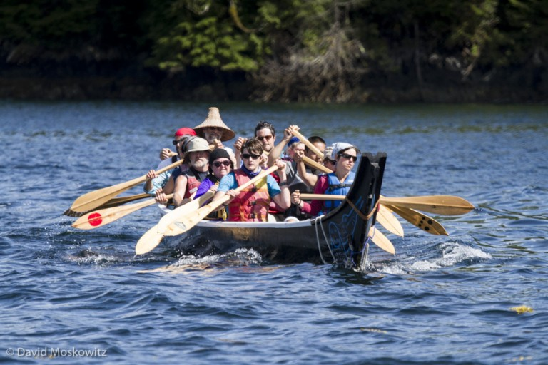 Members of the Blue Heron Canoe family and students of the LEAF school paddle the canoe along the shores of an island on the central coast of British Columbia.