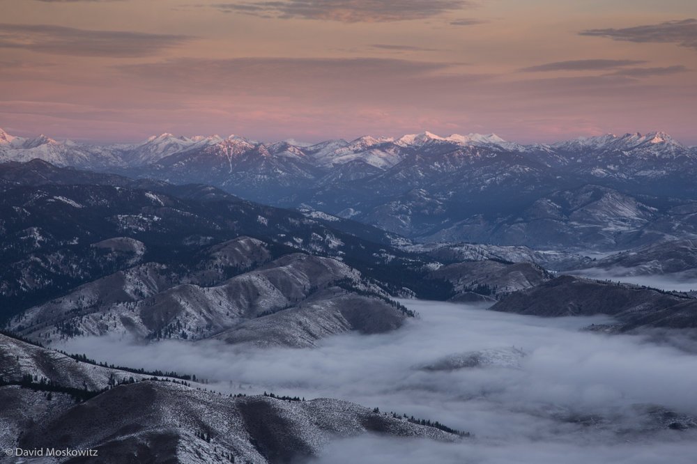 Low clouds cover the Methow Valley as the first light of the day hits the high peaks of the Pasayten Wilderness on the eastern edge of the North Cascades.