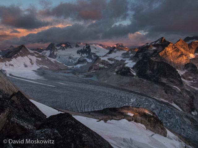 Sunrise over peaks to the North of the Bugaboo Range and the massive tongue of the Vowell glacier below them. As seen from the ridge between Bugaboo Spire and Crescent Spire.