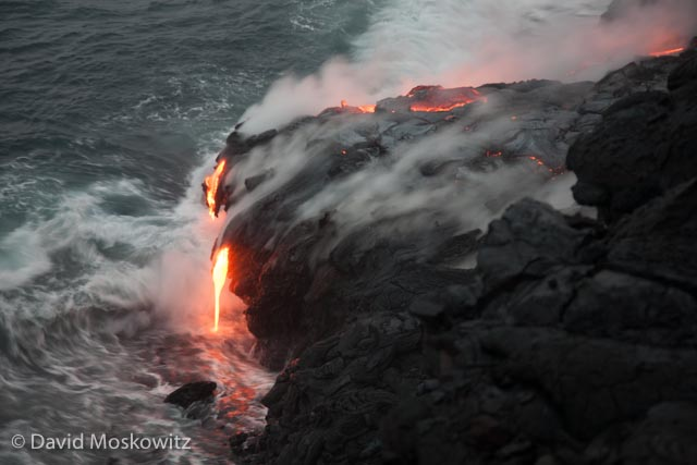 Lava from the Kilauea Volcano on the big isalnd of Hawaii pours over cliffs into the Pacific Ocean.
