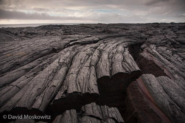 "The fluid arcing shape in this basalt is characteristic of the slow moving lava, referred to as ""pahoehoe"" in Hawaiian, which it was formed from. As the cooling rock contracts cracks such as this one form in the newly formed basalt."