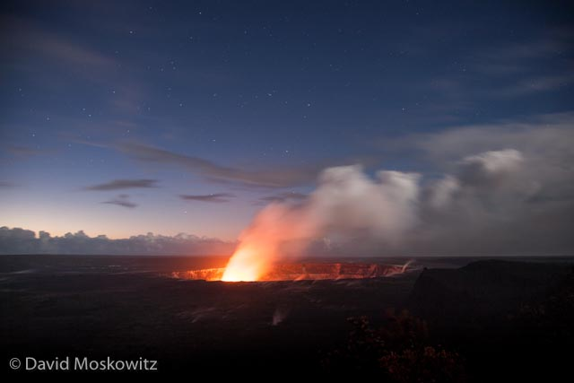 Morning light illuminates the eastern sky while stars still shine higher in the sky above the glowing cauldron of Kilauea's main crater on the big island of Hawaii.