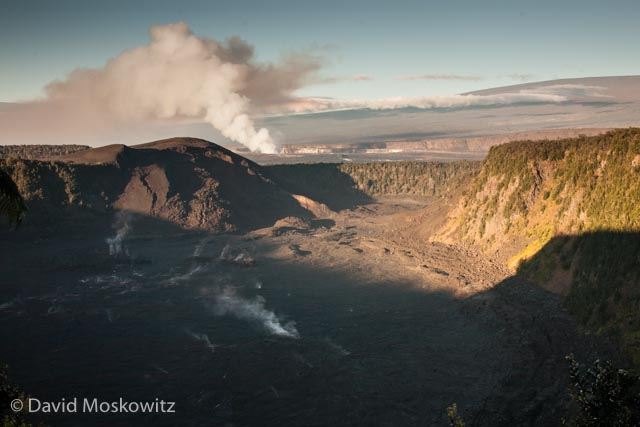 The current main crater of Kilauea smokes in the distance, beyond the still steaming floor of the Kiauea Iki crater, the remnants of a volcanic event from the 1950's in which the foreground crater filled with hundreds of feet of lava.