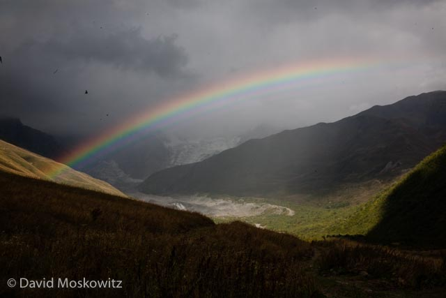 A rainbow straddles the mountain valley and snout of the valley glacier flowing off of the Shkhara massif. Georgian Caucuses Mountains.