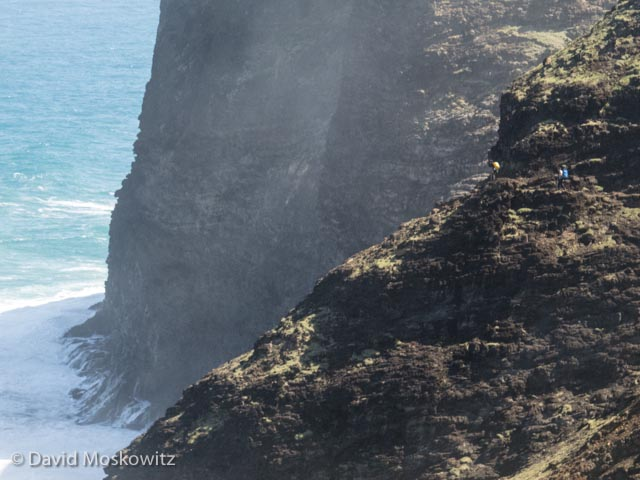 Hikers on the Kalalau trail, dwarfed by the cliffs and ocean beyond.