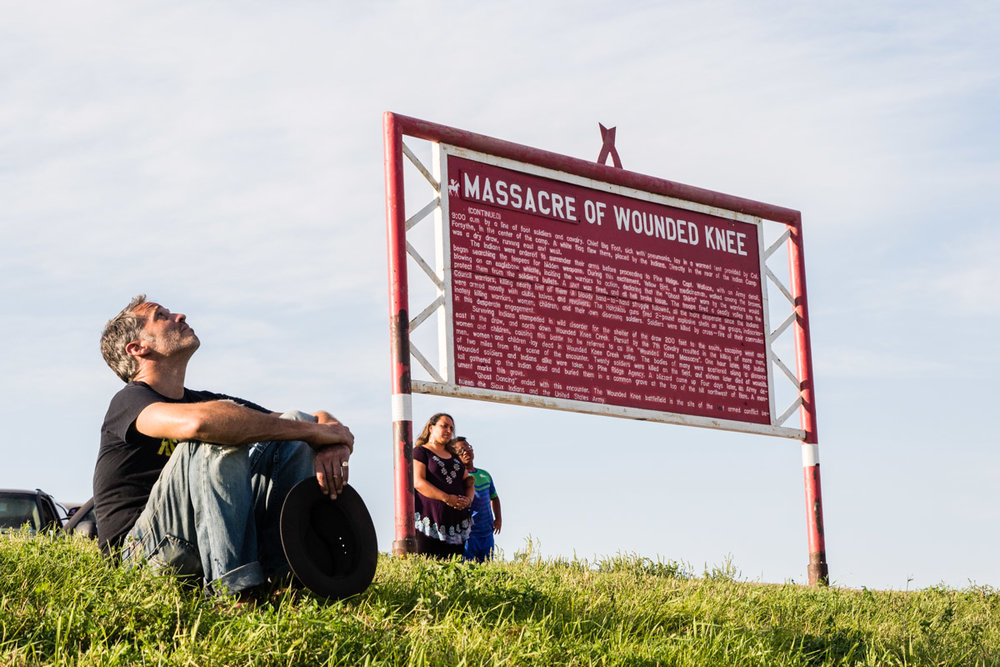 Will Scott and two other members of the gathering reflect at the site of the Wounded Knee Massacre. In 1890, the US military killed 146 Lakota men, women, and children who were camped here, the last armed conflict between the US military and the Lakota.