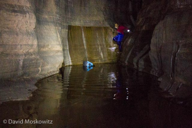 Downclimbing via headlamp light, Ian eases his way into the last pool of water, his dry bag floating nearby.