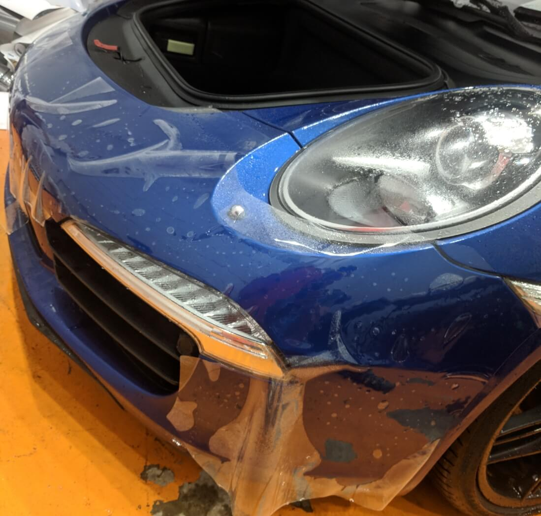 Porsche 911 getting pre-cut Xpel Ultimate paint protection film on front bumper
