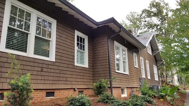 Shake siding and cottage-style windows make this simple home exterior outstanding. You can see, from the side view, how far back the space extends.