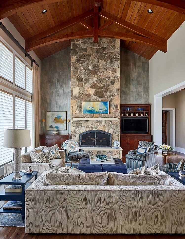 Living area with tall stone fireplace and architecture