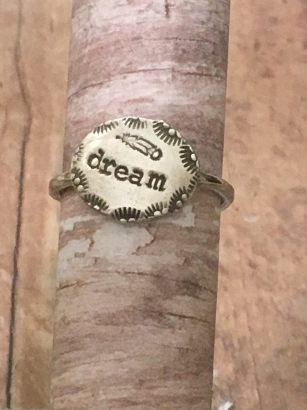 "Dream Silver Ring with Feather  The word ""dream"" sits front and center on this simple silver ring. A beautifully decorated border with a feather accent this everyday ring. $42.00"