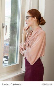 Attraktive Geschäftsfrau schaut im Büro aus dem Fenster