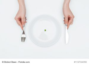 Closeup of hands of young woman eating one small green pea using knife and fork over white background