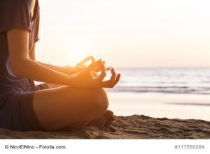 Girl relaxing with yoga on the beach at sunrise, gyan mudra