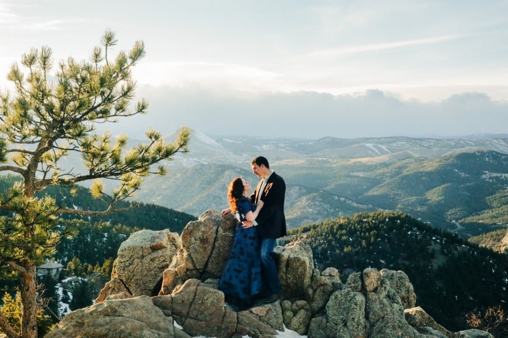 couple embracing on top of a mountain with a huge Rocky Mountain landscape view.jpg