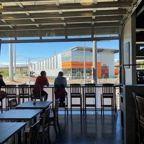 Mt. Hood Brewery's new spot offers beers, pizza, a refurbished caboose as a dining room, and a front-row seat of the Orange Line and train museum across the street.