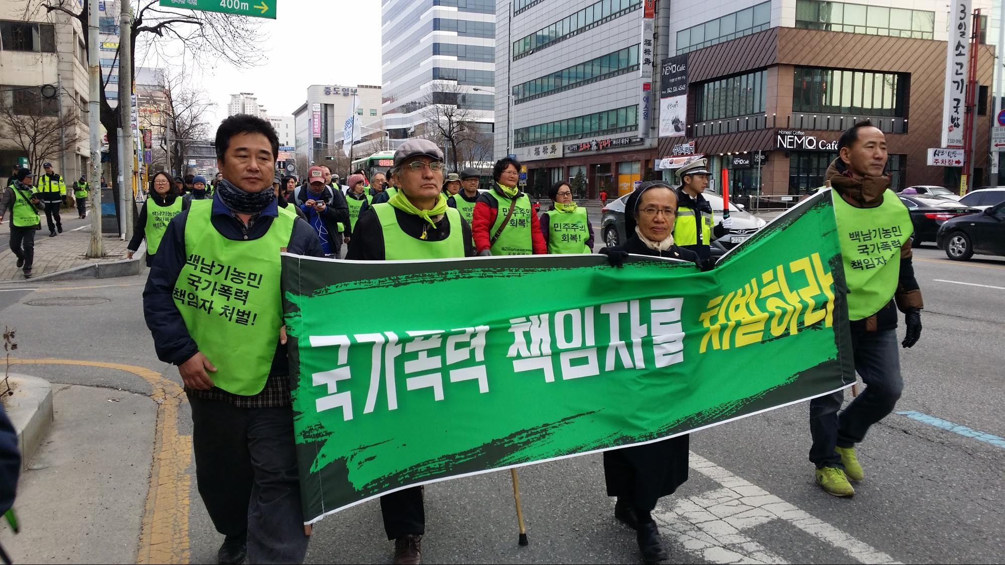 "The participants holding banner and walked on the road. The banner reads ""Those who are responsible for state violence must be punished."""