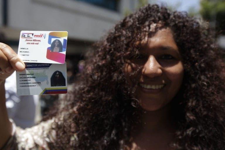 경제전쟁에 대응하기 위한 정책중 하나인 까르네뜨 데 라 빠뜨리아라고 부르는 카드를 베네수엘라 여성이 들어 보이고있다. (출처: albaciudad.org)