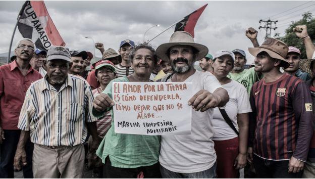 """400km를 행진한 농민들이 """"토지에 대한 사랑은 어떻게 토지를 지킬지, 어떻게 토지가 죽지 않도록 확실히 지켜주는가 하는 것이다… 농민 행진은 위대하다""""고 쓴 피켓을 들고 있다. (출처: dataurgente.com)"""