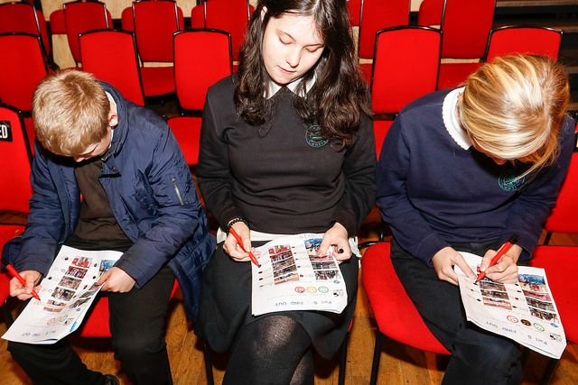 Three young school students fill in their Arts Award forms at Oska Bright Film Festival.