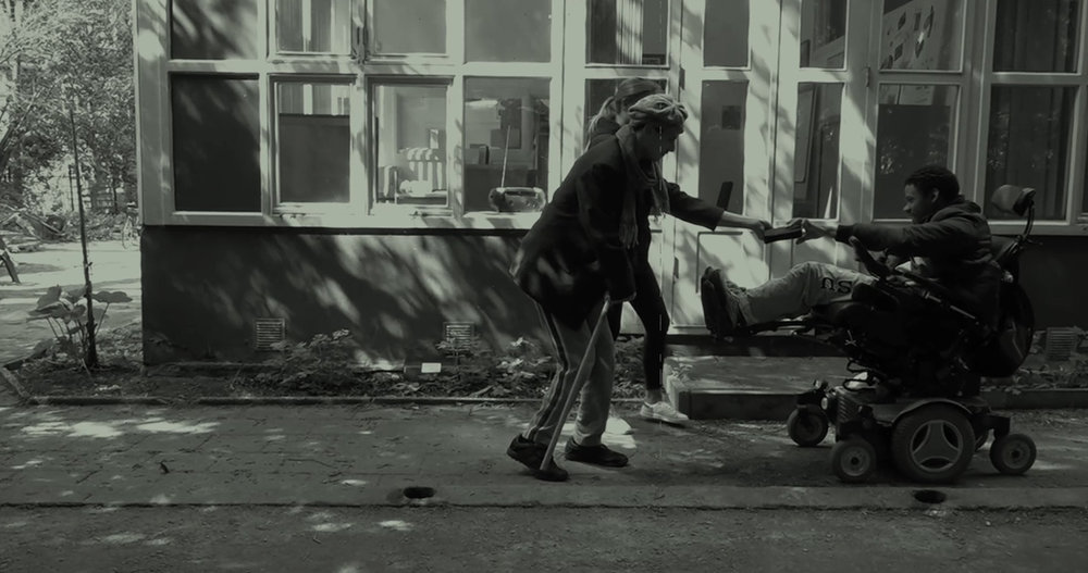 A man with a walking stick and a man in a wheelchair head for a collision. A still from short film Brahim's Slapstick.