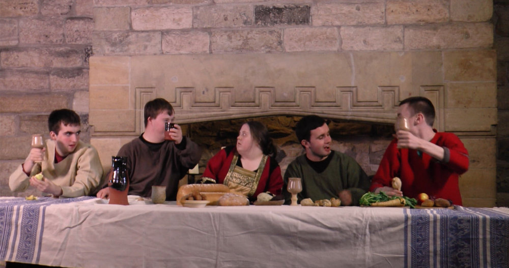 People dressed up in historical outfits enjoying a drink along a long table. A still from short film, Bruce.