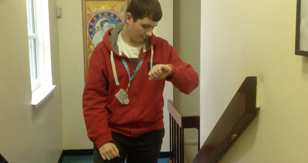 A teenage boy checks his watch at the top of a flight of stairs. A still from short film, Cup of Tea.