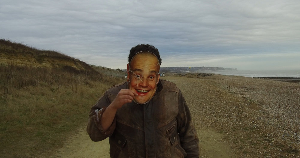 A man walks along a coastal path wearing an Al Murray mask. A still from short film, The Mask.