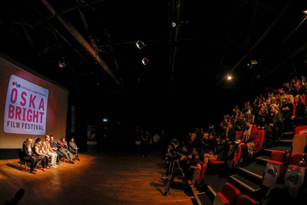 A panel of learning disabled filmmakers give a Question & Answer session for a full audience at the Oska Bright Film Festival. They sit in front of a screen.